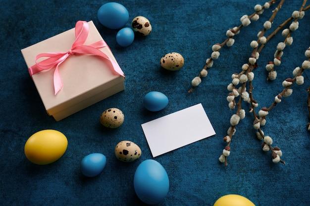 柳の枝、イースターエッグ、ギフトボックス。春の木の開花とパスカル料理、休日のお祝いのための新鮮な花の装飾、イベントのシンボル