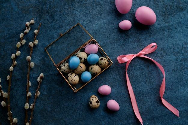 柳の枝、装飾的なギフトボックスのイースターエッグ。春の木の開花とパスカル料理、休日のお祝いのための新鮮な花の装飾、イベントのシンボル