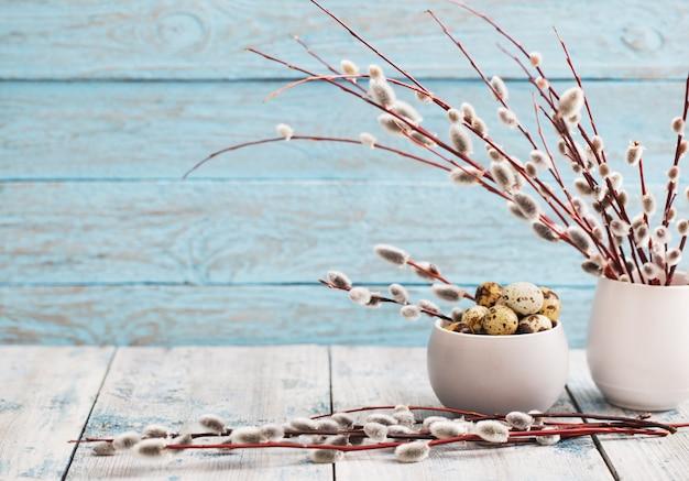 柳の枝とウズラの卵の木製の背景