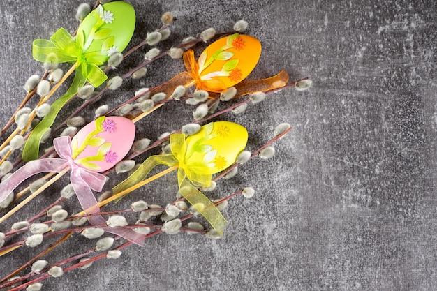 灰色のコンクリートの背景にカラフルな卵のイースターの装飾と柔らかいふわふわの銀色の柳の木の枝。