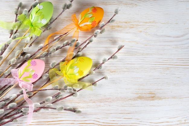 Ветвь дерева ивы с мягким пушистым серебристым с красочным украшением пасхи яиц на белой деревянной предпосылке.