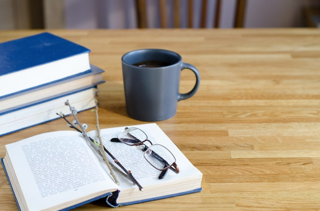 柳の小枝とメガネが開いた本の上にあります。木製のテーブルには、本のスタックと一杯のコーヒーがあります。