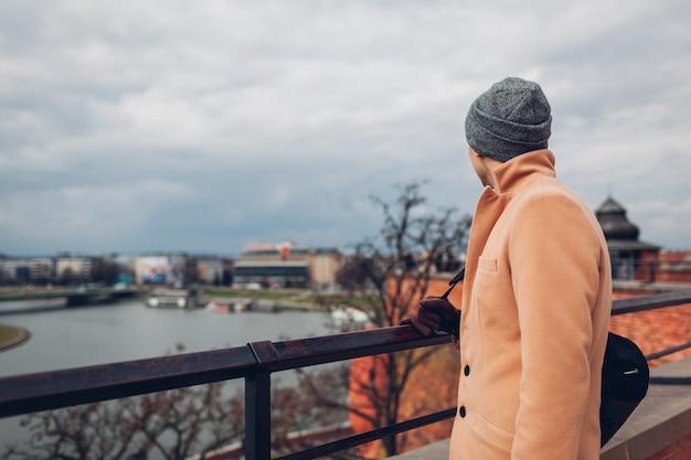 ポーランド、クラクフのヴァヴェル城からのウィルサ川の眺め。街の風景を楽しんで歩く男の観光客。