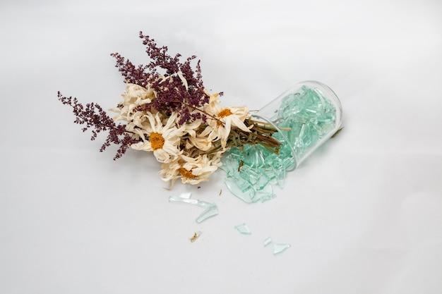 しおれた花束は、秋の壊れた夢の白の壊れたガラスの花瓶の概念で古い花を乾かします