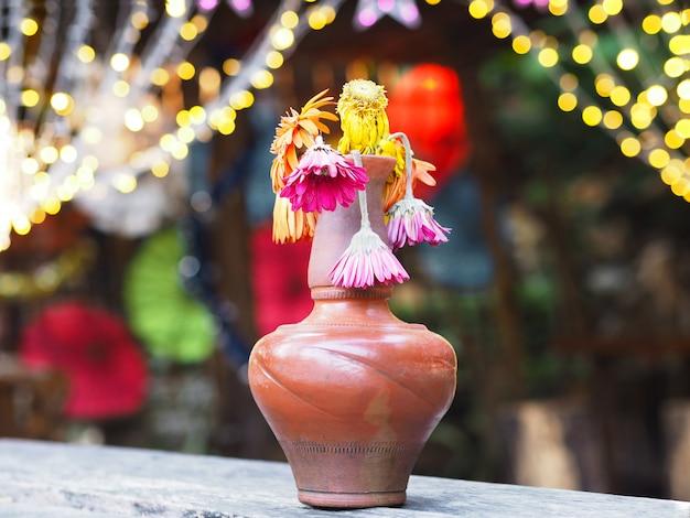Wilted gerbera flower in brown vase on wooden table
