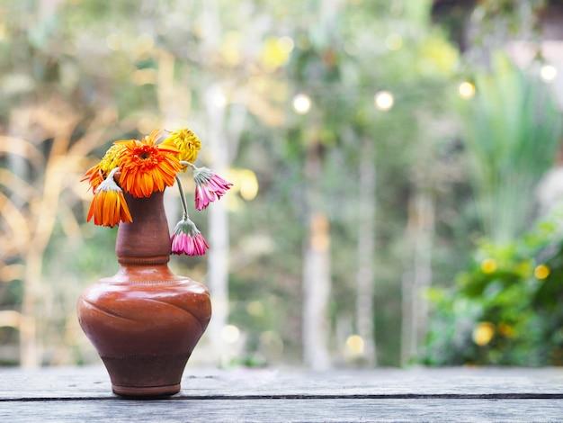 木製のテーブルの上に茶色の花瓶にしおれたガーベラの花。
