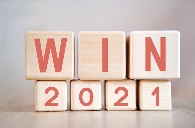 Win 2021 on wooden cubes, on wooden background