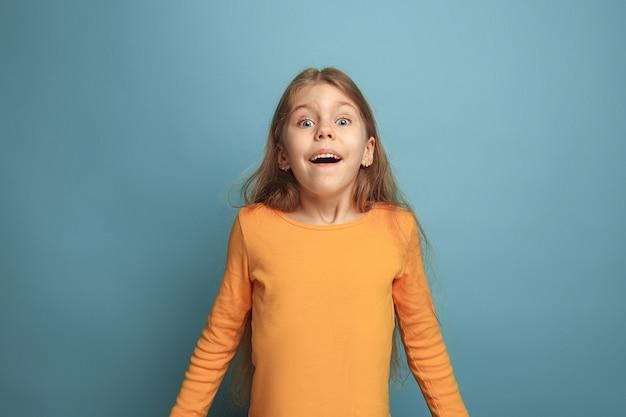 승리-감정적 인 금발 십대 소녀는 행복의 모습과 이빨 미소를 가지고 있습니다.