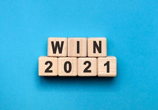 Win-グラデーションの青い背景を持つ木製の立方体のテキストの概念