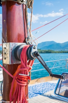 The winch is attached to the red mast of the yacht