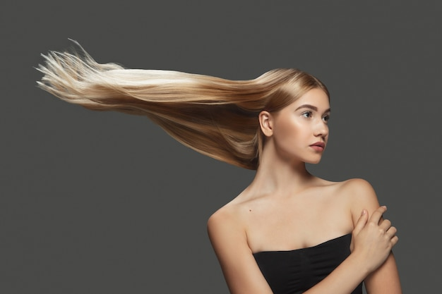 Wind. beautiful model with long smooth, flying blonde hair on dark grey studio background. young caucasian model with well-kept skin and hair blowing on air. concept of salon care, beauty, fashion.