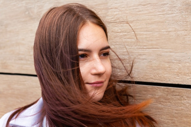 Wind blowing young woman long brown hair