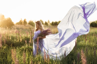 Wind blows pregnant woman's violet dress while she stands in the field of lavender