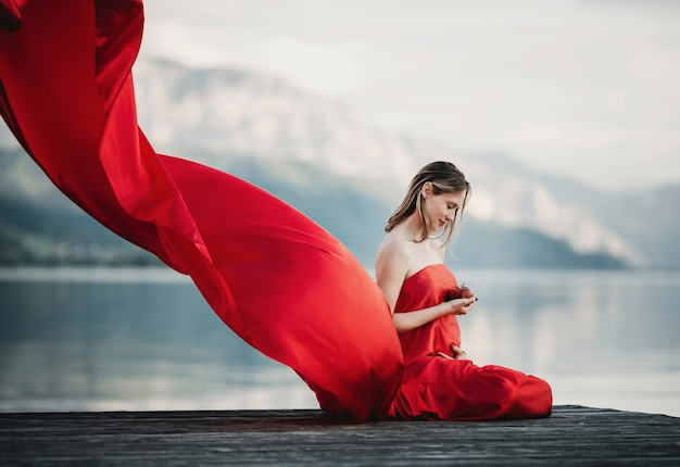 Wind blows red dress of a pregnant woman sitting with apple on the bridge over the lake