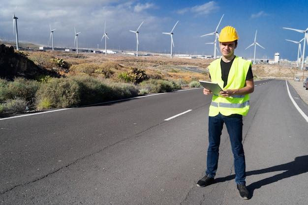 風力エネルギーの概念、風力タービンの前に立つエンジニア、グリーンエネルギー、環境にやさしい産業