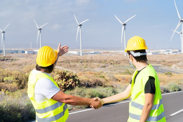 Wind energy concept, two engineers shaking hands in front wind energy mills farm, eco friendly industry concept