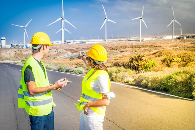 Wind energy concept, two engineers standing in front wind energy mills farm and showing at it, eco friendly industry concept during corona virus pandemia