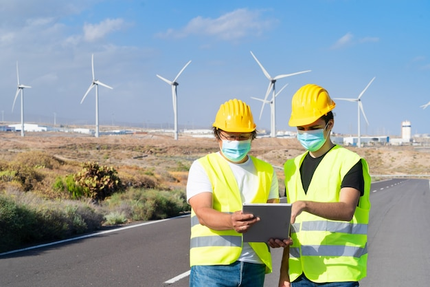 風力エネルギーの概念、風力エネルギー工場の農場の前に立つ2人のエンジニア、環境にやさしい業界の概念