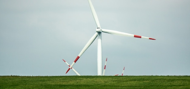 Wind fan standing on a green landscape during daytime