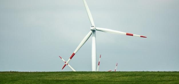 Вентилятор ветра, стоящий на зеленом пейзаже в дневное время