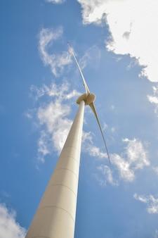 Wind field with wind turbines, producing wind energy under blue sky