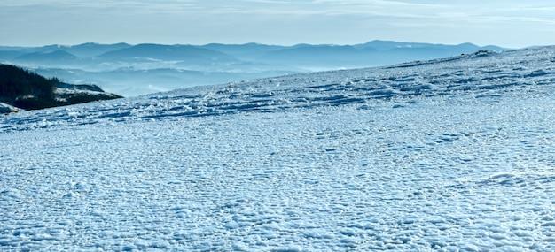 Ветер формирует ледяную структуру на поверхности зимнего горного снега в противоположном направлении света