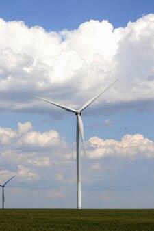 Ветрогенератор на пшеничном поле против голубого неба с грозовыми облаками в солнечный день