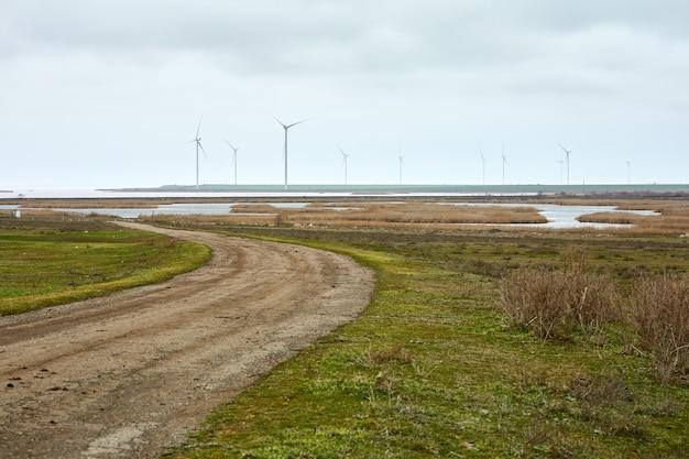 회색 하늘을 배경으로 흐린 날씨에 분홍색 물이 있는 호수 기슭의 풍력 발전기.