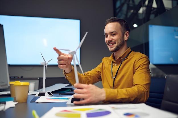 テーブルの上の風車モデル。若いマネージャー、itオフィスで開発中のアイデア。専門的なチームワークと計画、グループブレーンストーミングと企業活動、同僚とのミーティング