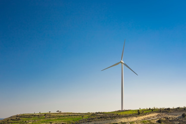 明るい夏の日の風車。風力タービンが発電する緑の牧草地。