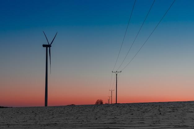 Ветряная электростанция в поле рядом с линией электропередачи на закате