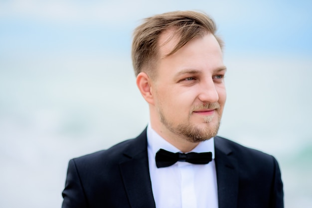 Wind shakes groom's hair standing on the beach with waves splashing behind him