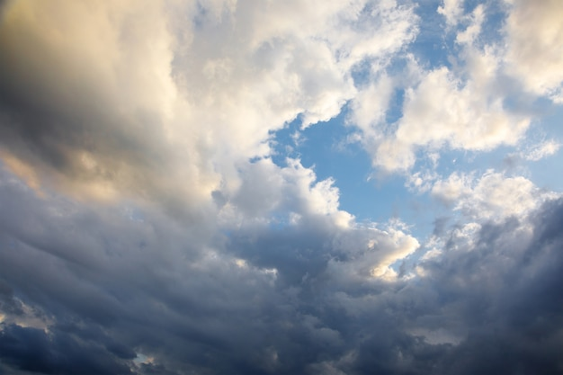 The wind spins white-blue cumulus clouds on a blue sky on a summer evening.
