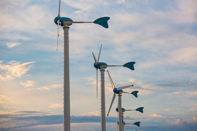 再生可能なクリーンエネルギーを生成するための大きな緑の野原の青い空に風力タービンを建設