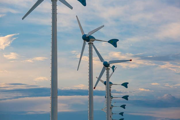 Строительство ветряной турбины в большом зеленом поле и голубом небе для производства возобновляемой чистой энергии
