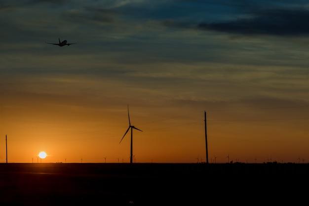 再生可能エネルギーの仕事を示すカラフルな夕日の風力タービンファーム、風力エネルギーがテキサス西部に吹き込む