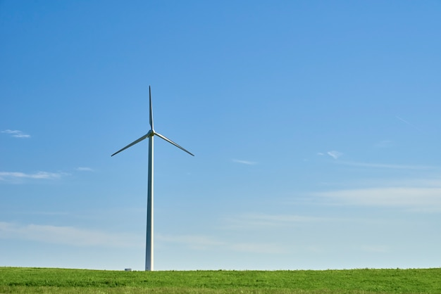 Wind turbine on a field with green grass