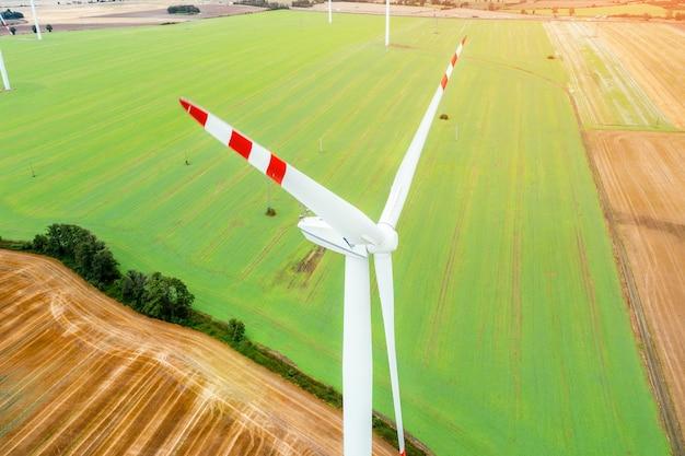 전기를 생산하는 풍력 터빈, 녹색 들판의 배경에 있는 풍차, 대체 에너지원, 드론에서 보기