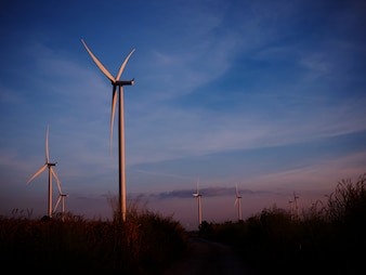 Wind turbine in grass field with twilight