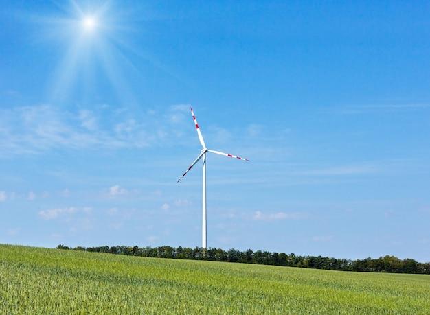 青い太陽の光る空の背景に風力タービン