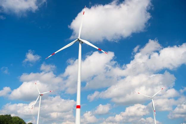 曇った青い空の風力タービン。代替エネルギーおよび電力源。地球温暖化。気候変動と生態学。エコパワーとグリーンテクノロジーのコンセプト。