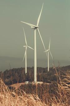 푸른 흐리게 산 위에 갈색 잔디에 풍력 터빈
