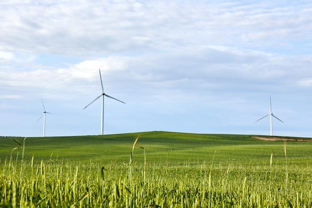 青い曇り空の上の緑の芝生の風力タービン。風力タービン-再生可能エネルギー源。