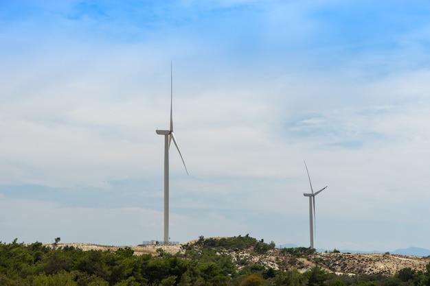 青い曇った空の上の緑の草の上の風力タービン
