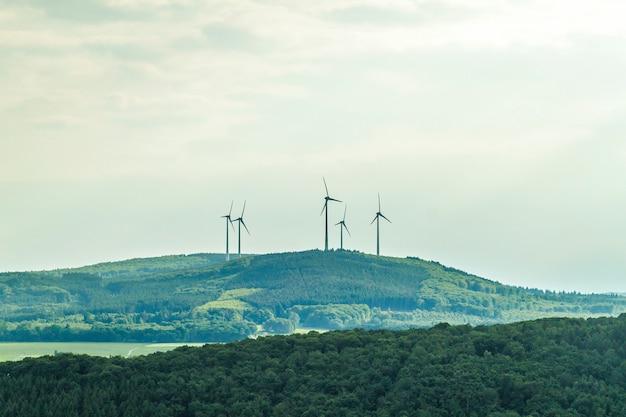風力タービンの再生可能エネルギー源の夏の風景で、澄んだ青い空と前景のフィールド