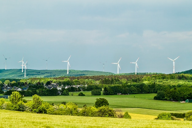 Wind turbine renewable energy source summer landscape with clear blue sky and a village or town in the foreground