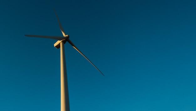 Ветряк, вид с низкой точки, который стоит на плоском лугу на фоне голубого неба .. эко сила. ветряные турбины, вырабатывающие электроэнергию