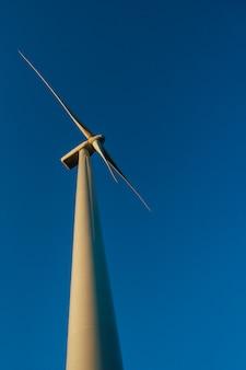 青い空を背景に平らな牧草地に立つ、低い視点から見た風力タービン。