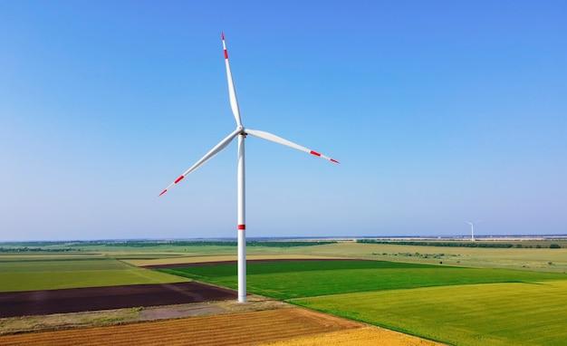 晴れた秋の日の緑の野原にある風力タービン。