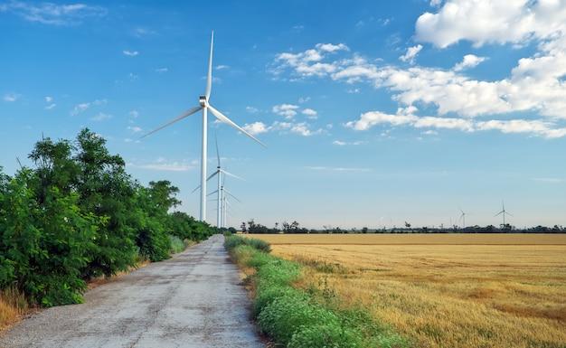 風力タービンと夏の曇りの日に農業分野。エネルギー生産、クリーンで再生可能なエネルギー。